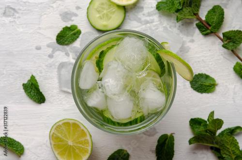 Fototapeta Infused water on a glass. Detox water mix of cucumber, lemon, lime and mint. obraz na płótnie