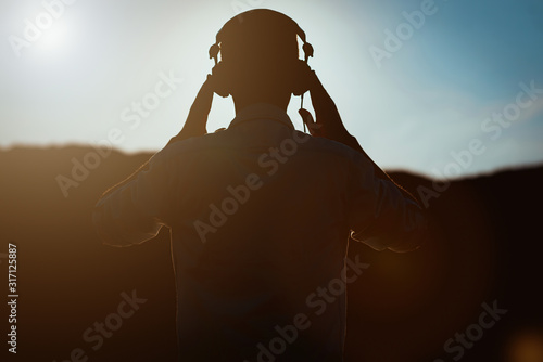 Photo Silhouette of man with headphones on sunset sky background