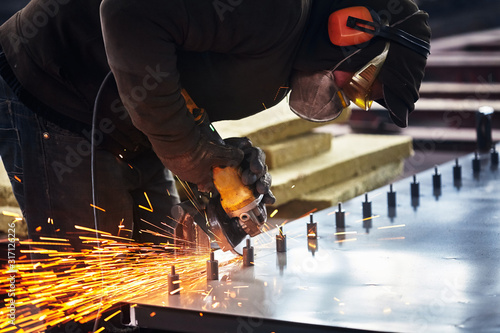 Heavy industry worker cutting steel with angle grinder Wallpaper Mural