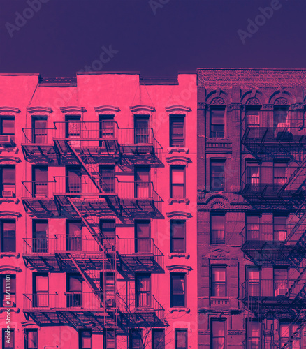 Fototapeta Fire escapes on the exterior of old buildings in New York City in pink and blue color obraz
