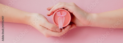Fotografía  Round pink gift box in women's hands on a pink background