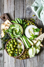 A Dipping Board With Olives, Cucumber, Dips, Bread, Crackers And Nuts.