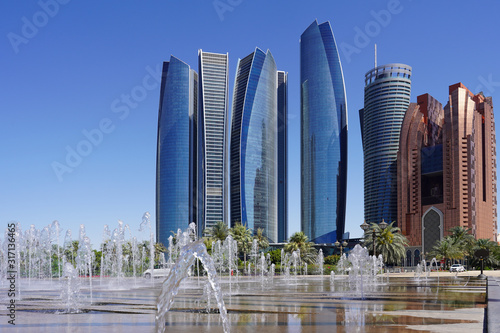 view of a row of scyscraper in abu dhabi behind a fountaion, beautiful blue sky Wallpaper Mural