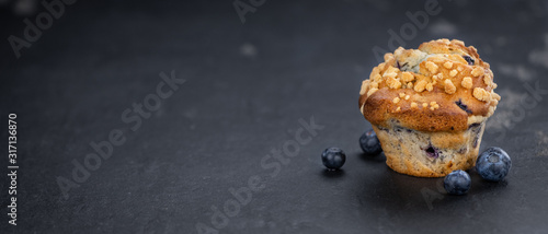 Photo Fresh made Blueberry Muffins on a slate slab (close-up shot; selective focus)