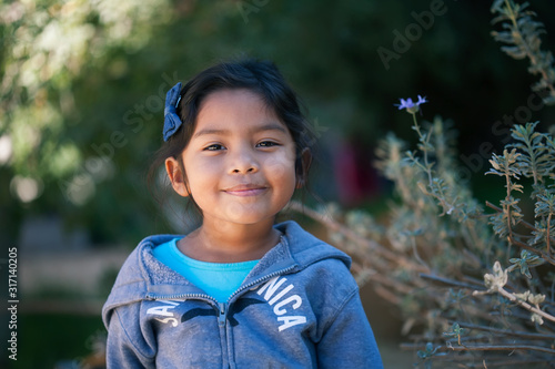 Photo Confident little girl wearing a sweater, standing in front of trees and green plants with a sincere smile on her face