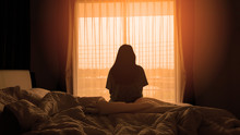 Silhouette Of Woman Sitting On The Bed Beside The Windows With Sunlight In The Morning