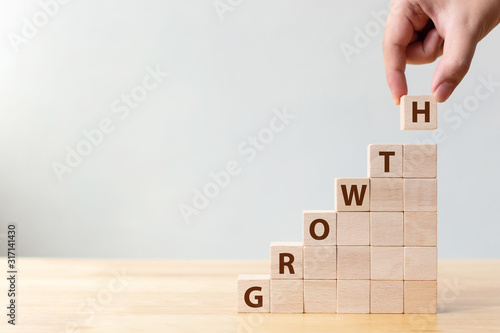 Ladder career path for business growth success process concept.Hand arranging wood block stacking as step stair with word GROWTH