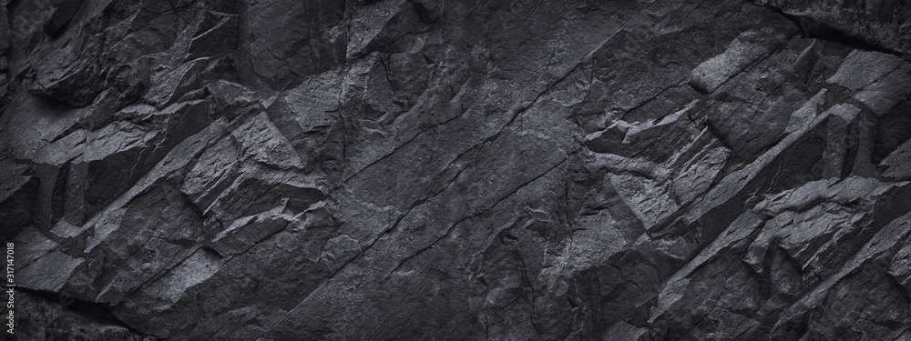 Fototapeta Black stone background. Dark gray grunge banner. Black and white background. Mountain texture. Close-up. Volumetric. The rocky backdrop. Abstract black rock background. Detail.