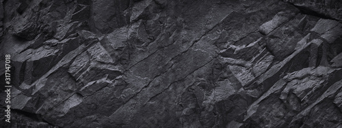 Fototapeta Black stone background. Dark gray grunge banner. Black and white background. Mountain texture. Close-up. Volumetric. The rocky backdrop. Abstract black rock background. Detail. obraz