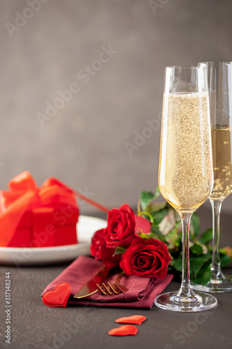 Fototapeta Champagne glasses, a bouquet of roses and a gift on a dark background. Romantic celebration of Valentine's day obraz