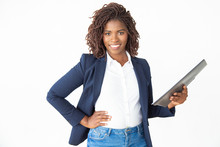 Businesswoman Holding Folder And Smiling At Camera. Cheerful Confident Young Businesswoman Standing With Hand On Waist And Holding Papers On White Background. Paperwork Concept