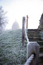 Vertical Shot Of Stairs Up The Hill With A Church In The Distance In A Fog