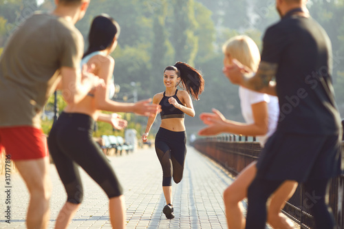 Obraz Girl runner runs fun with a group of friends in a park - fototapety do salonu