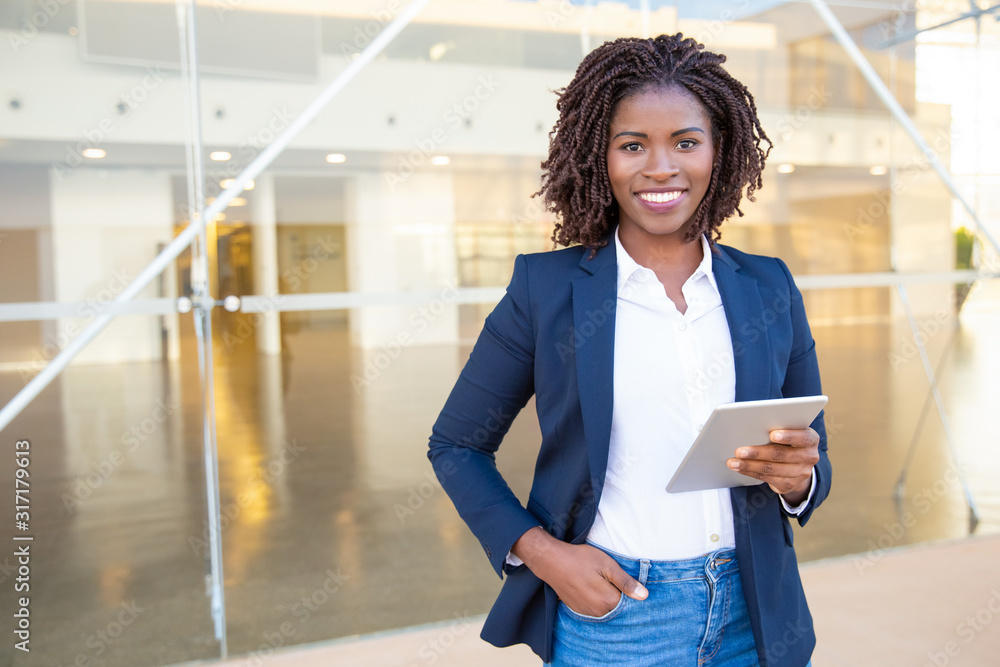 Fototapeta Businesswoman holding tablet pc and smiling at camera. Cheerful young African American businesswoman holding digital tablet and looking at camera. Wireless technology concept