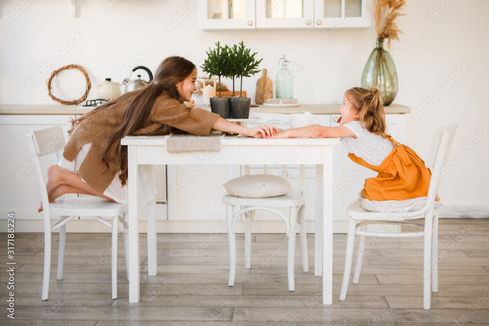 Fototapeta Two sisters play in a bright, stylish kitchen. Beautiful interior.
