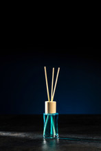 Air Freshener, Reed Diffuser And Aromatherapy Concept - A Bottle Of Home Fragrance Standing On A Stone Countertop On A Beautiful Dark Blue Background. Copy Space.