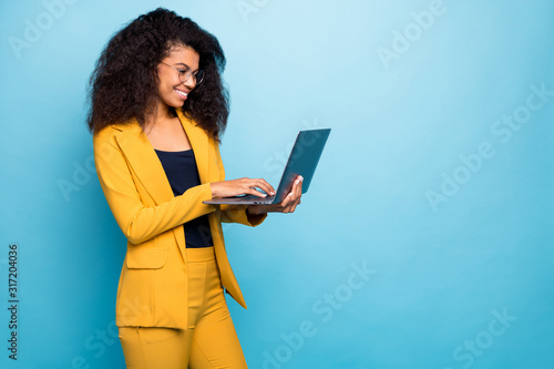 Fototapeta Profile photo of pretty assistant dark skin wavy lady holding notebook searching information internet help boss wear specs yellow suit blazer pants isolated blue color background obraz