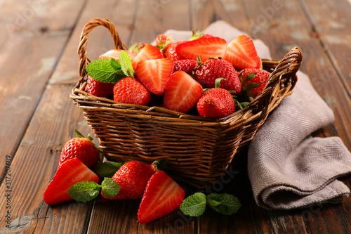 Obraz wicker basket with juicy strawberry on wood background - fototapety do salonu