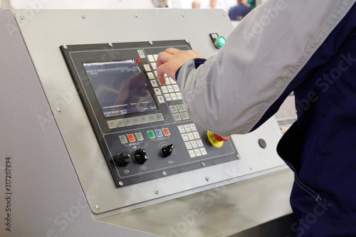 Hand of a working man on the control panel of the machine in the factory Canvas Print