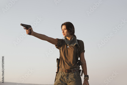 Canvastavla Woman Standing With a Gun Outdoors in Desert