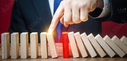 Businessman restarts the process of falling dominoes Canvas Print