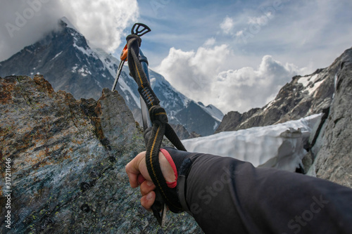 Photo Mountain climber's hand with Ice tool (ice axe) on the rock on the background of alpine landscape
