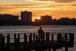 A silhouetted man fishing off a pier in the Halifax River in Daytona Bearch, Florida as the sun rises over the skyline of condominiums on the beachfront.