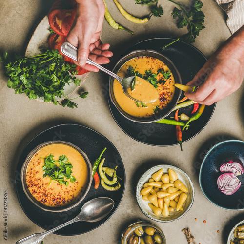 Photo Flat-lay of man eating turkish traditional lentil soup Mercimek , vegetables, flatbread, pickled pepper over concrete background, top view, square crop
