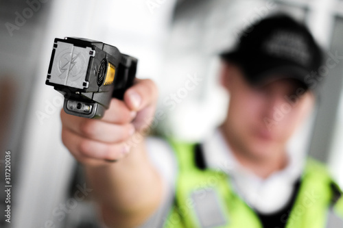 Fototapeta Closeup view of a loaded stun gun in a hand of a young man wearing high visibili