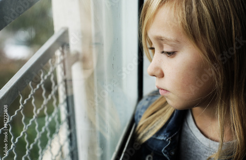 Portrait of a 9 year old sad girl who is sitting next to a window