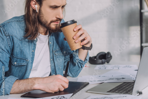 Photo bearded of animator in wireless earphones holding paper cup