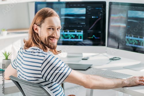 Fototapeta cheerful bearded art editor working in studio