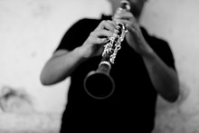 Grey Scale Shot Of A Person Playing Clarinet In Front Of A White Wall