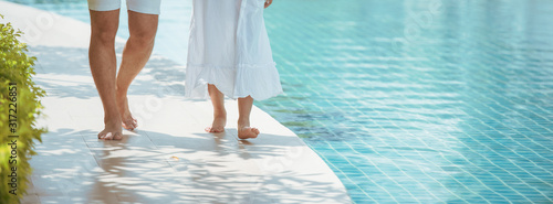 Fototapeta Young couple walking together by the pool. obraz