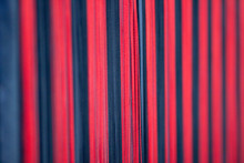 Red And Black Vertical Threads On The Wall