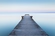Wooden dock near the sea with the fog in the background