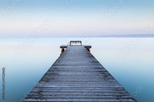 Fototapeta Wooden dock near the sea with the fog in the background obraz
