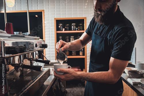 Barista preparing cappuccino on espresso machine for customer in coffee shop Canvas Print