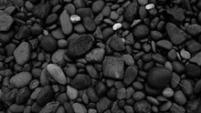 Black Pebbles On The Beach Bac...