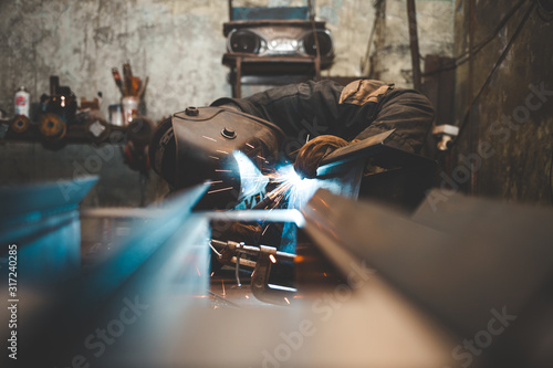 Worker in a welder mask works in a workshop for welding iron Canvas Print