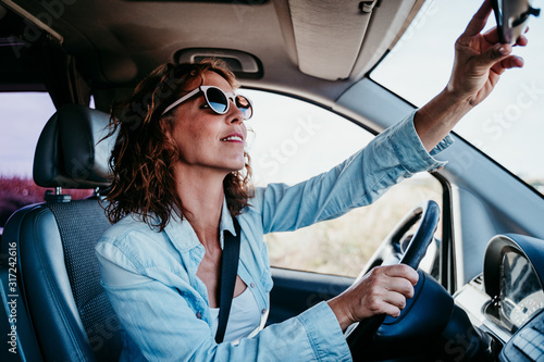 young beautiful woman driving a car and adjusting rear mirror Canvas Print