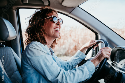 Leinwand Poster young beautiful woman driving a car. travel concept