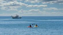 Two Kayakers With Greek Fishing Boat At Anchor In The Background Off The Coast Of Lesvos