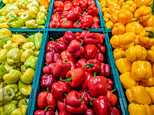 Fototapety, obrazy: Colorful bell peppers in green, red and yellow colors stacked in market grocery store for sale as a part of a healthy vegetarian vegan diet