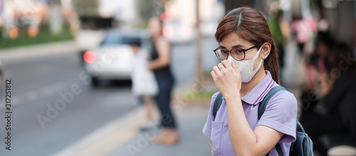 Fototapeta young Asian woman wearing N95 respiratory mask protect and filter pm2.5 (particulate matter) against traffic and dust city. healthcare and air pollution concept obraz