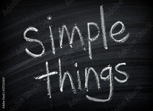 Fototapeta The phrase Simple Things written by hand on a blackboard as a reminder