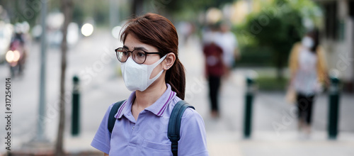 Fotomural young Asian woman wearing protection mask against flu virus in the city