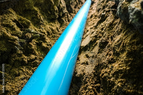laying PVC water pipe under backfilling sand trench with dark background by clos Tableau sur Toile