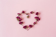 Heart Symbol Made Of Dry Rose Flower Buds On Pink Background. Flatlay, Top View Valentine's Day Minimal Holiday Concept.
