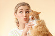 Beautiful young woman with cute cat on color background